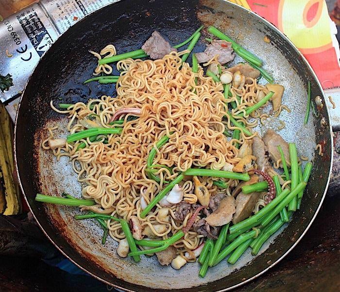 Cho mì tôm vào trộn đều, thêm thịt bò và rau củ vào xào chín